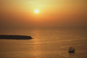 夕暮れの海と帆船のシルエット